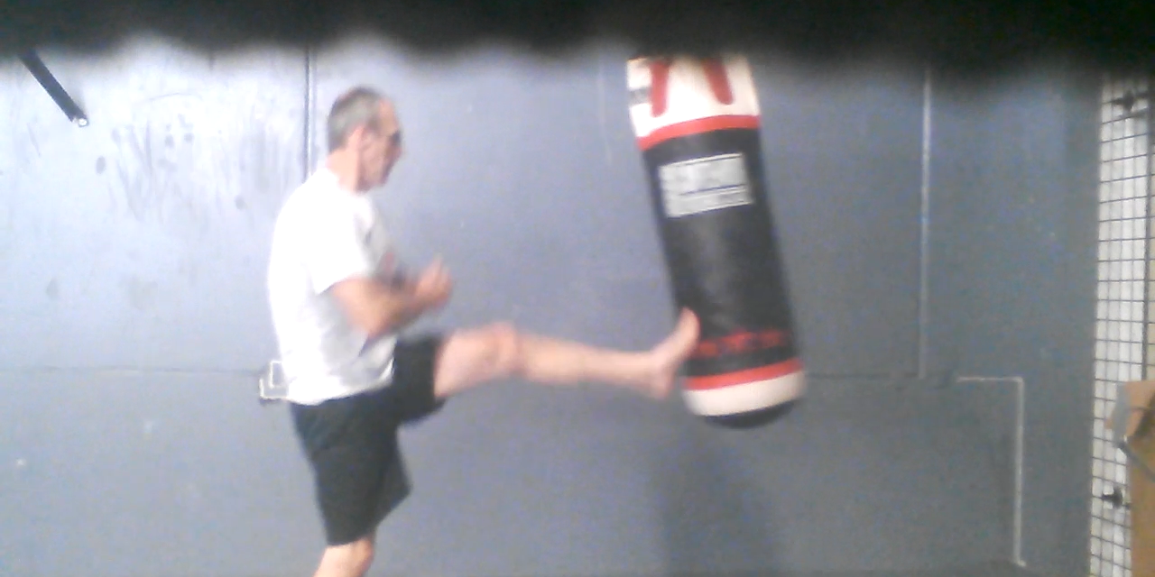 Punching and kicking a heavy bag for fitness